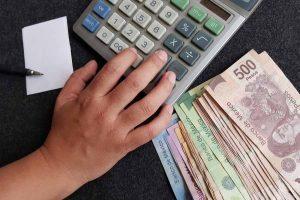 Hombre usa calculadora para calcular impuestos o gastos. Al lado hay billetes en pesos mexicanos.