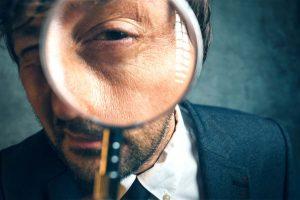 Hombre mirando a través de una lupa.