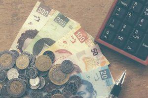 Varios billetes y monedas de pesos mexicanos frente a una calculadora.