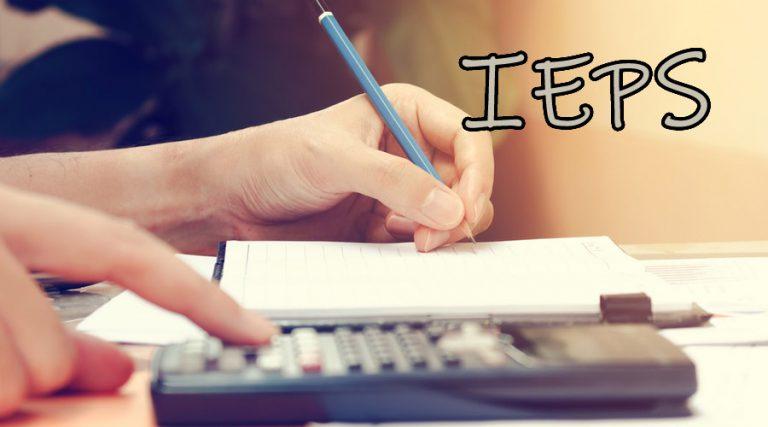 Mujer calculando el IEPS 2019 en una calculadora y tomando anotaciones.