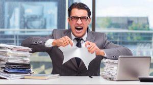 Oficinista o burócrata enojado en un escritorio lleno de papeles que le mentó la madre a clientela, rompe hoja.