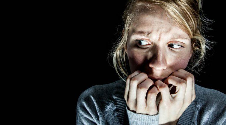 Percepción de riesgo, mujer rubia asustada comiéndose las uñas sobre fondo negro