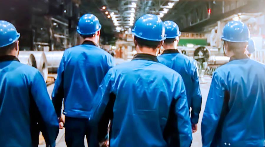 Obreros con cascos y chamarras azules caminando hombro con hombro. Contrato colectivo de trabajo.
