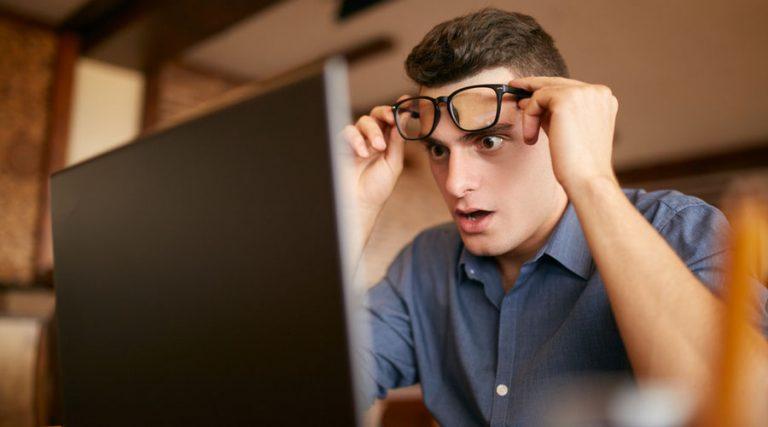 hombre asustado mira su laptop mientras levanta sus lentes por aviso del SAT en materia antilavado