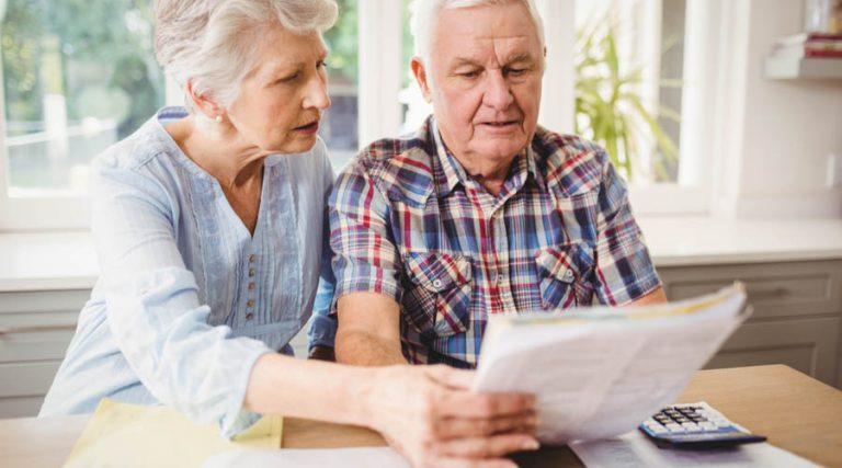 pareja de ancianos jubilados haciendo cuentas de su pensión con la UMA o el salario mínimo